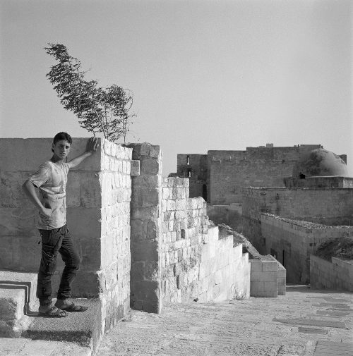 Youth poses against wall in Aleppo Citadel