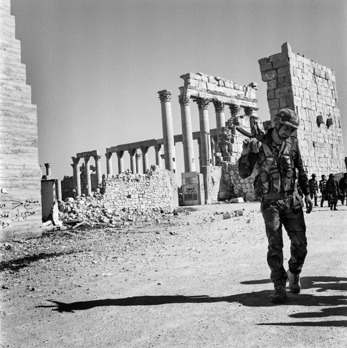 Victorious Syrian Soldier With Gun on Shoulder Outside the Entrance to the Antique City of Palmyra.  Graffiti on the Wall shows the Recent Presence of Daech.