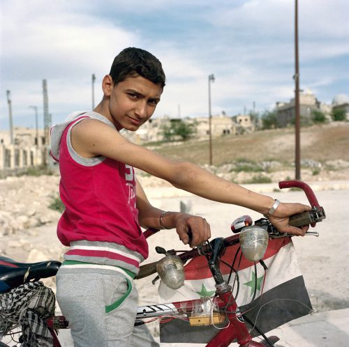 Adolescent on bike with Syrian flag, Aleppo 2017